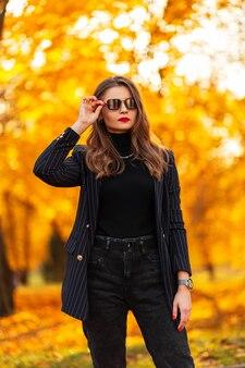 Bella giovane donna con occhiali da sole vintage in abiti alla moda con una giacca alla moda, maglione nero e jeans passeggiate nel parco con fogliame autunnale arancione al tramonto. elegante stile autunnale femminile