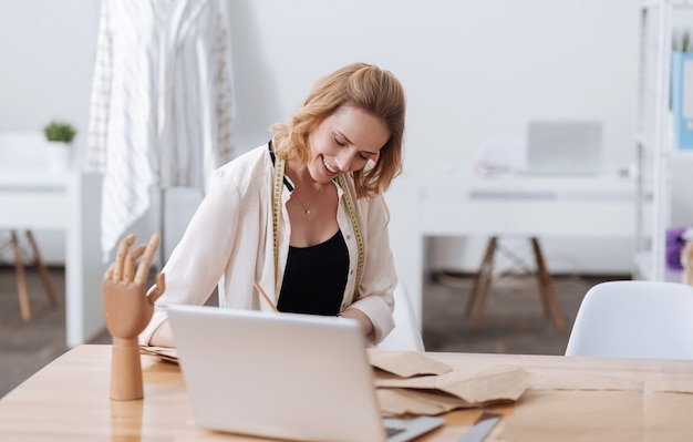 Piuttosto giovane donna che lavora al suo nuovo progetto e sembra felice mentre è seduto al tavolo pieno di modelli.