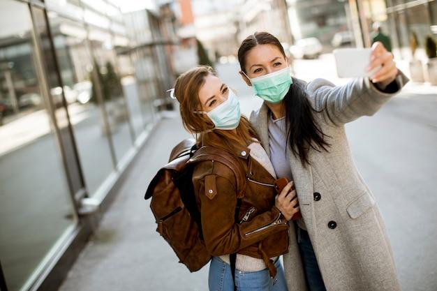 Giovani donne graziose con la maschera facciale protettiva sulla via