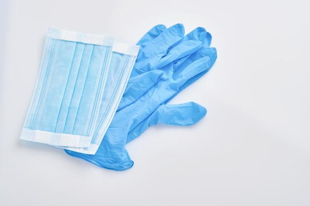Prevenire il coronavirus. maschera protettiva medica e guanti monouso isolati su priorità bassa bianca.