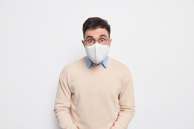 Prevenire la diffusione del virus. l'uomo scioccato indossa una maschera facciale consiglia di indossare misure protettive durante la pandemia di coronavirus vestito con un maglione