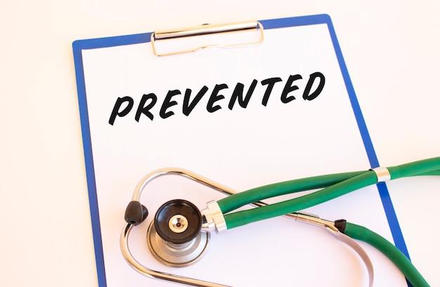 Prevenuto - testo sulla cartella medica con documenti e stetoscopio