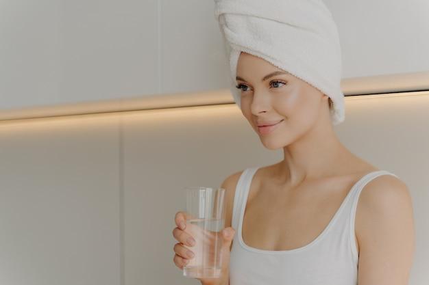 Prevenire la disidratazione. immagine di una giovane bella donna con la pelle fresca e luminosa che beve acqua al mattino subito dopo la doccia con un asciugamano avvolto sulla testa seduta in una cucina di colore chiaro