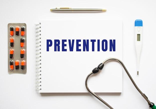 Prevenzione è scritto in un taccuino su un tavolo bianco accanto a pillole e uno stetoscopio