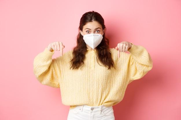 Misure preventive, concetto di assistenza sanitaria. donna eccitata in respiratore medico che punta le dita verso il basso a copyspace, mostrando promo, in piedi contro il muro rosa.