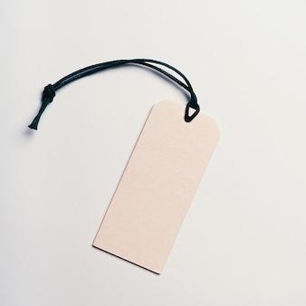 Cartellino del prezzo in cartone è vuoto senza iscrizioni su uno sfondo chiaro.