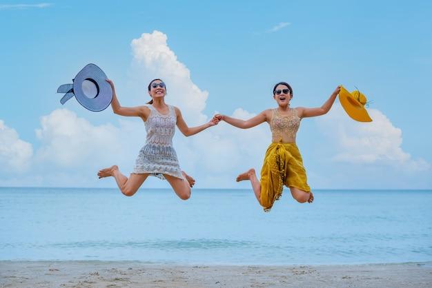 L'orgoglio e la coppia d'amore lgbtq sulla spiaggia estiva. bisessuali e omosessuali viaggiano insieme in vacanza.