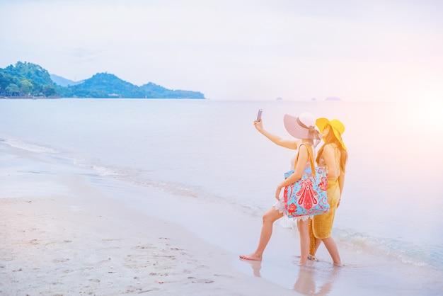 Orgoglio e lgbtq+ sulla spiaggia estiva. coppia d'amore bisessuale e omosessuale. usa lo smartphone per la foto dell'attività.