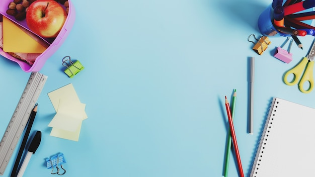 Concetto piatto di scuola primaria con materiale scolastico assortito, blocco note, penna, matita, mercati, adesivi, graffette e scatola per il pranzo con panino, noci e mela su superficie blu