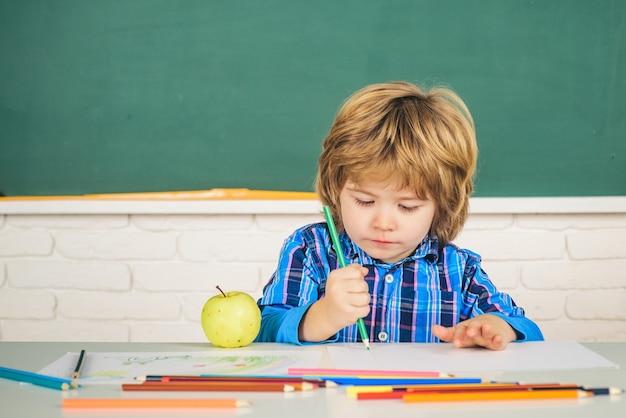 Allievo della scuola primaria bambino vicino alla lavagna nell'aula scolastica bambini felici della scuola a lezione