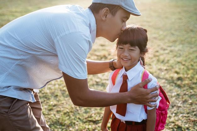 Una studentessa della scuola elementare bacia la mano di suo padre quando va a scuola