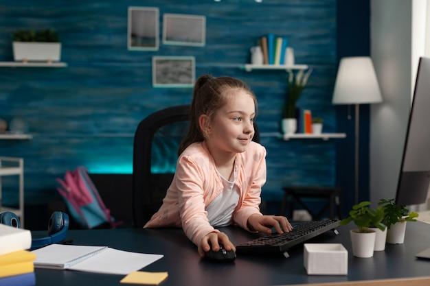 Studentessa della scuola elementare che guarda il monitor del computer