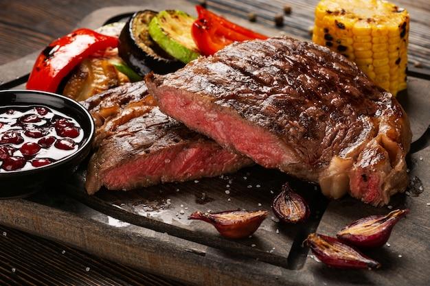 Prime black angus ribeye bistecca con verdure grigliate e salsa di mirtilli rossi su tavola di legno