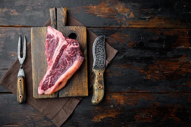 Prime bistecca con osso crudo tenero tagliato per un set barbecue, sul tagliere di legno, sul vecchio tavolo di legno scuro