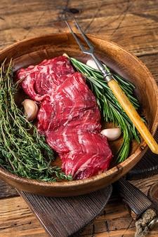 Prime raw bistecca di manzo con gonna machete in piatto di legno con erbe. fondo in legno. vista dall'alto.