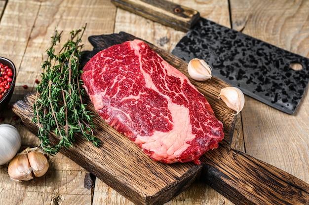 Prime rib eye bistecca di carne di manzo crudo su un tagliere di legno da macellaio con mannaia