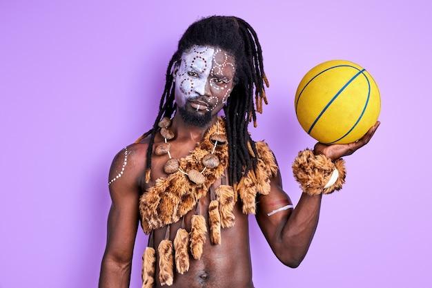 Uomo primitivo in abbigliamento autentico nazionale che tiene la palla gialla nelle mani, andando a giocare a basket