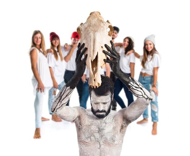 Primitivo uomo che offre cranio cavallo