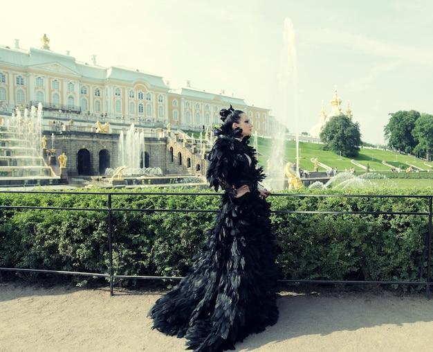 Principessa nel parco vicino alla fontana e al palazzo