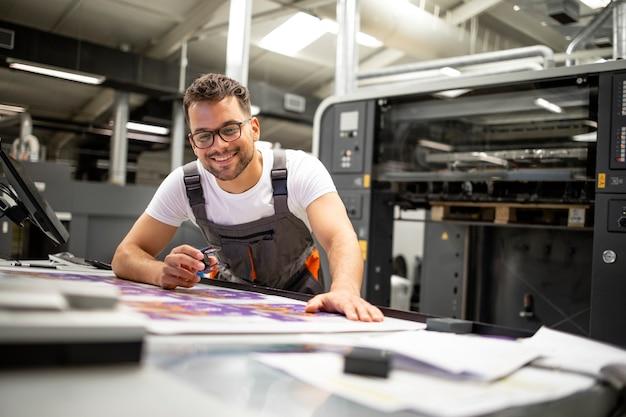 Addetto alla stampa che controlla la qualità del processo di stampa e controlla i colori con la lente di ingrandimento.