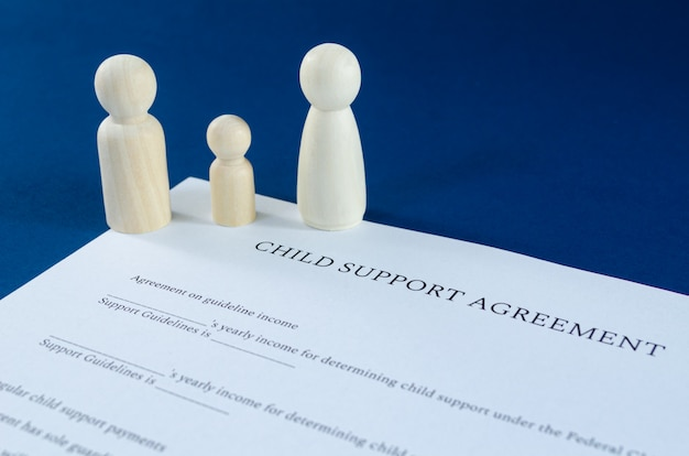 Accordo stampato di sostegno all'infanzia con figure in legno uomo, donna e bambino in un'immagine concettuale per il sostegno all'infanzia finanziario. su sfondo blu.