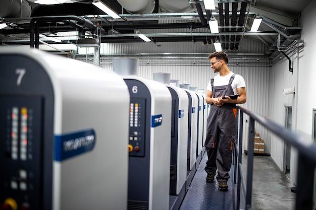 Interno della tipografia con moderna macchina da stampa offset e processo di controllo della stampa da parte dell'operatore