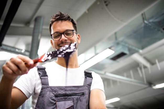 Operatore della macchina da stampa che mescola la vernice prima di aggiungere il colore alla macchina da stampa offset