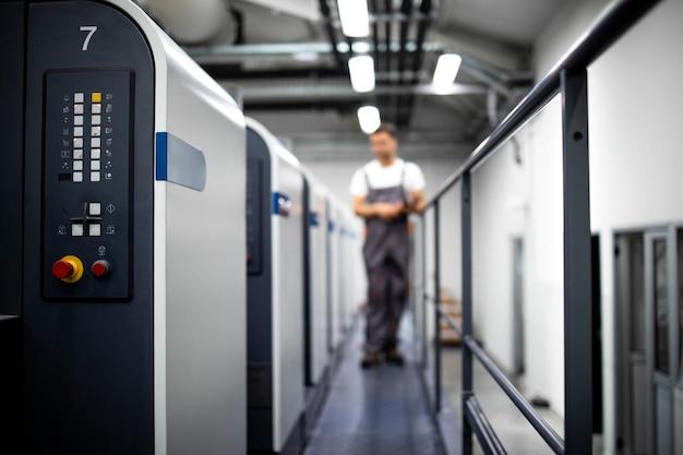 Macchina da stampa e operatore in uniforme di lavoro che controlla la qualità e il processo di controllo della stampa