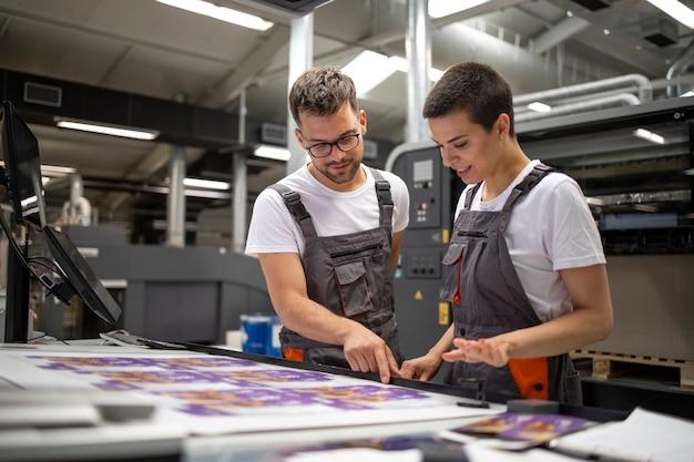 Operatori della macchina da stampa che controllano la qualità grafica e i valori del colore presso la tipografia.