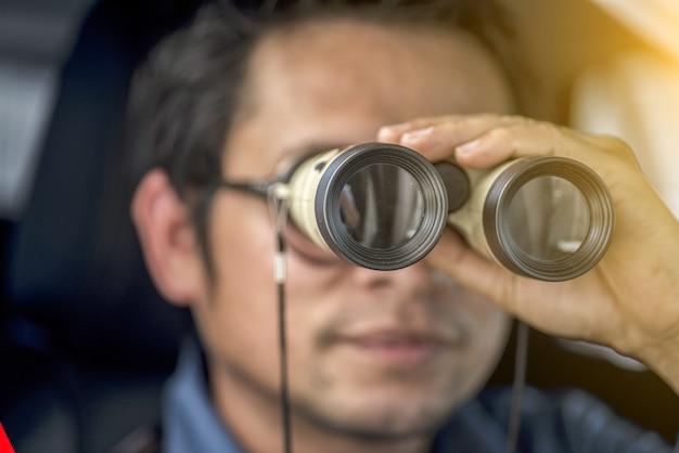 Agente investigativo privato che si siede all'interno della macchina fotografica dell'automobile con la macchina fotografica di slr