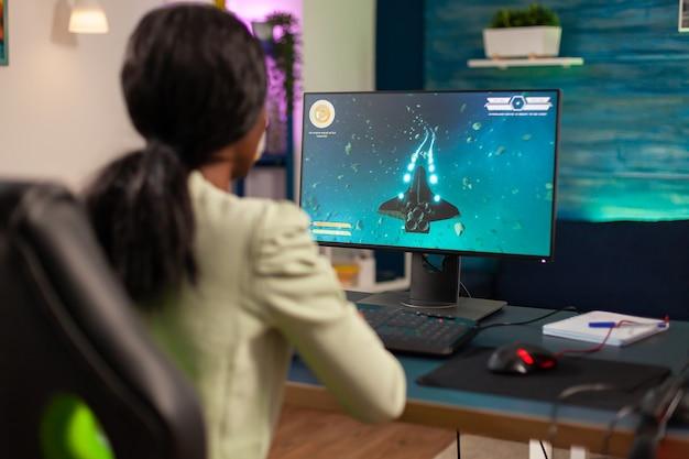 Pro giocatore africano che gioca a sparatutto spaziale con joystick wireless di notte. la donna competitiva del giocatore informatico che esegue un torneo di videogiochi usa un joystick professionale.