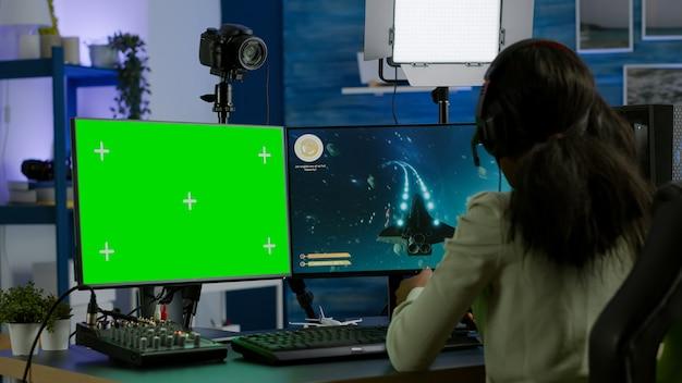 Giocatore di pro donna africana che gioca su un computer potente con schermo verde finto chroma key durante lo streaming della competizione online. giocatore che utilizza un pc con giochi sparatutto in streaming desktop isolati con schermo verde