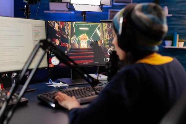 Giocatore professionista seduto su una sedia da gioco alla scrivania e parlando al microfono per la competizione di videogiochi sparatutto spaziale. donna in streaming videogiochi online per torneo esport in sala con luci al neon