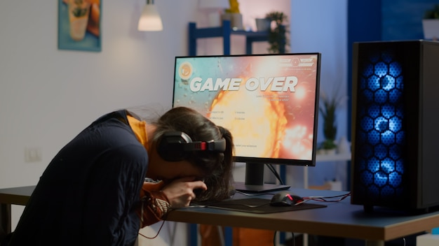 Giocatore professionista donna che perde la competizione di videogiochi sparatutto spaziale su un potente computer professionale con controller wireless. giocatore professionista in streaming gioco online utilizzando joystick e headse professionali