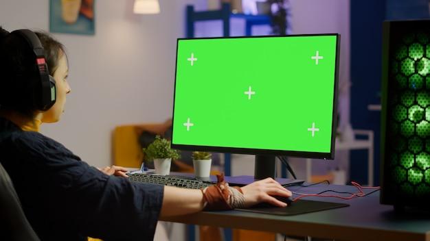 Giocatore professionista donna che gioca su un computer potente con schermo verde finto chroma key durante lo streaming della competizione online. giocatore che utilizza un pc con giochi sparatutto in streaming desktop isolati con schermo verde