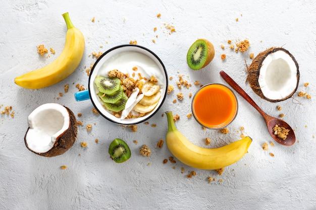 Concetto di cibo probiotico. ciotola di yogurt di cocco fatto in casa con vista dall'alto di frutta fresca e muesli. cibo vegano sano. colazione gustosa e salutare