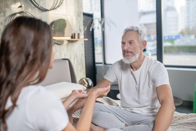 Problema, conversazione. uomo dai capelli grigi in ascolto serio in maglietta bianca che si siede con le spalle alla finestra e lo persuade