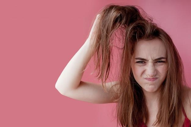 Problema del cuoio capelluto, ragazza grassa e sporca dei capelli, concetto di cura dei capelli