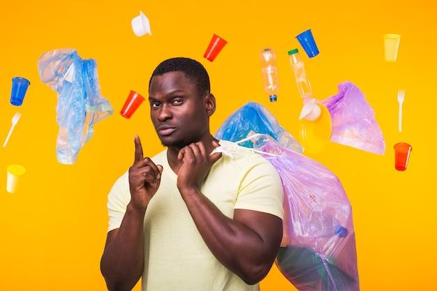 Problema di spazzatura, riciclaggio della plastica, inquinamento e concetto ambientale - uomo afroamericano che trasporta spazzatura per il riciclaggio e rivolto verso l'alto sulla parete gialla.