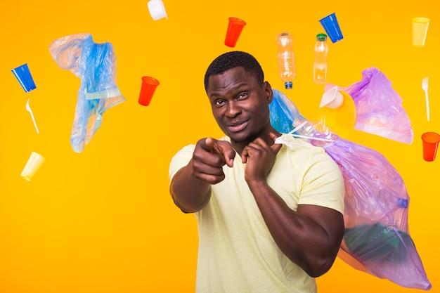 Problema di spazzatura, riciclaggio di plastica, inquinamento e concetto ambientale - uomo afroamericano divertente che trasporta spazzatura per il riciclaggio e che punta su di te sul muro giallo.