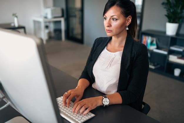 Problemi in azienda. donna di affari seria che digita sulla tastiera.