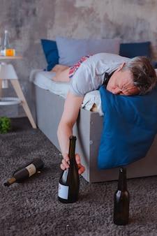 Problemi con l'alcol. uomo maturo ubriaco che tocca la bottiglia e che dorme sul letto
