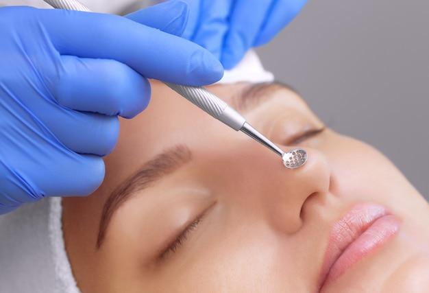 Procedura per pulire la pelle del viso con un apparecchio in acciaio con un cucchiaio da punti neri e acne