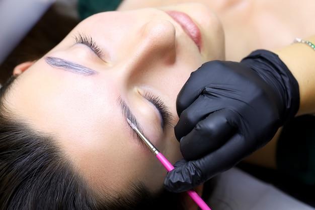 La procedura per lo styling delle sopracciglia a lungo termine è ravvicinata, il maestro applica la composizione per la laminazione delle sopracciglia con un pennello