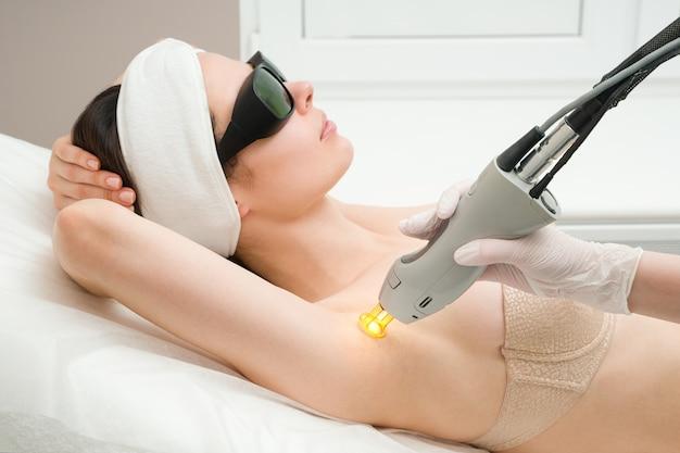 La procedura per la rimozione dei peli sul corpo di una donna in una depilazione laser clinica di cosmetologia