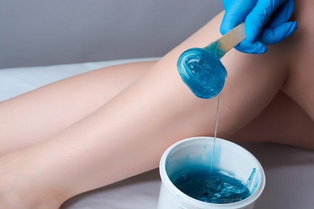 La procedura di shugaring gambe. l'applicazione della pasta di zucchero blu. la depilazione nel salone.
