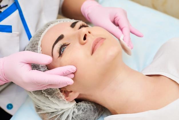 Il processo di applicazione di una crema sul viso di una bella ragazza