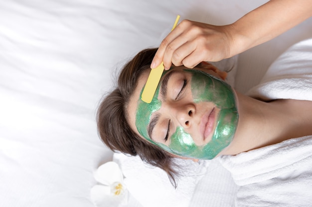 Il processo di applicazione di una maschera cosmetica verde sul viso di una giovane donna, procedura spa nel salone, bellezza e cura della pelle.