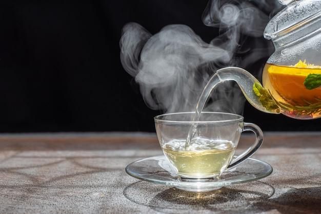 Processo di preparazione del tè, umore scuro il vapore del tè caldo viene versato dal bollitore in un bollitore con foglie di tè ribes rosso mandarino arancio limone, rosmarino, menta