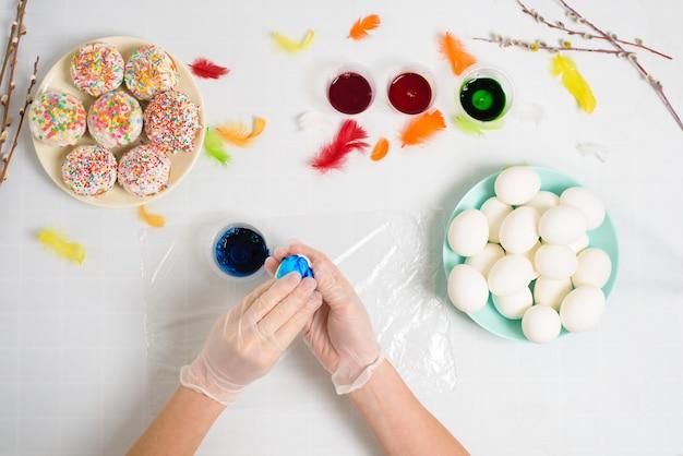 Processo di colorazione delle uova per la pasqua nei colori blu e rosso. una donna in guanti dipinge le uova con colorante da un barattolo, vista dall'alto, rami di salice e decorazioni di piume colorate.